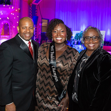 Group of three gala attendees smiling for the camera