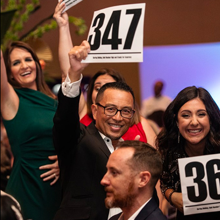 Gala attendees holding up auction bid signs